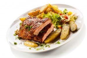 Rippchen mit Kartoffelecken, Gewürzgurken und Salat
