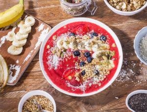 Smoothie-Bowl mit Erdbeeren, Banane, Kokos und Haselnüssen